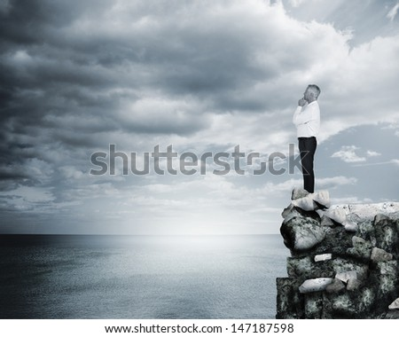 Thoughtful businessman standing at the edge of a cliff with the sea on the background
