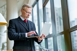Thoughtful businessman standing in cafe with modern laptop. Aged man in dark suit red tie and glasses.