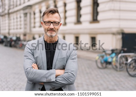 Thoughtful businessman standing staring at camera with folded arms in a cobbled urban street in front of a historic building
