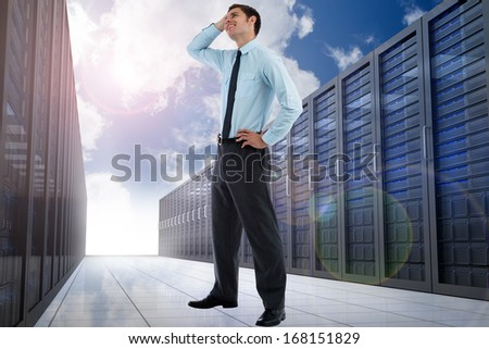 Thoughtful businessman with hand on head against server hallway in the sky
