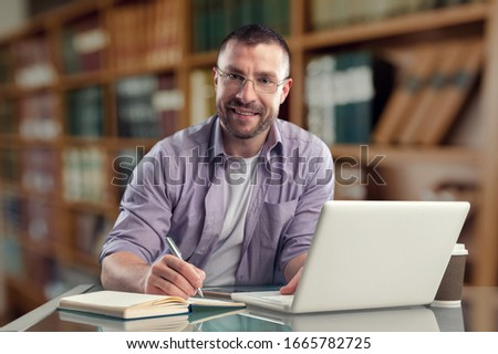 Thoughtful businessman working with laptop at the workplace