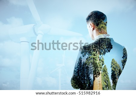 Thoughtful businessperson on sky background with wind mills. Double exposure. Eco friendly business concept #515982916