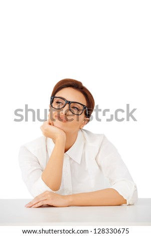 Thoughtful businesswoman wearing glasses sitting at her desk pulling a face as she contemplates a difficult decision