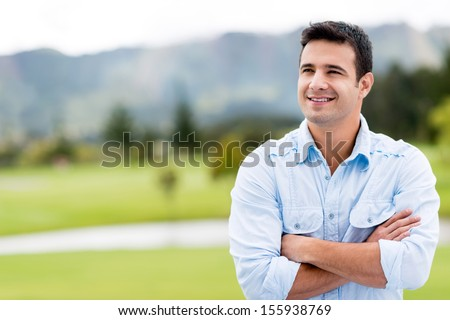 Thoughtful casual man outdoors looking up and smiling