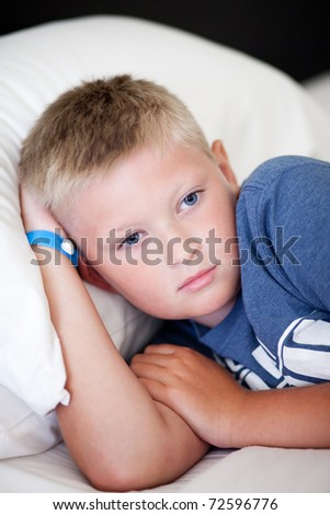 thoughtful child the boy lays on a bed