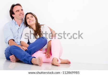Thoughtful couple sitting on the floor at home