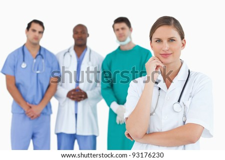 Thoughtful doctor with male colleagues behind her against a white background