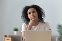 Thoughtful doubtful african female student worker looking away thinking solving problem feel lack of new creative ideas at work, pensive puzzled or bored young black woman sit at desk with laptop