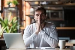 Thoughtful doubtful businessman in tension thinking make difficult decision at work, stressed man put hands in prayer pray with hope pondering reflecting concerned about problem challenge sit at desk