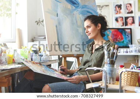 Thoughtful dreamy young European female artist bringing her creativity to life, sitting in her modern workshop interior with palette and painting knife. Hobby, job, occupation, art and craft concept #708327499