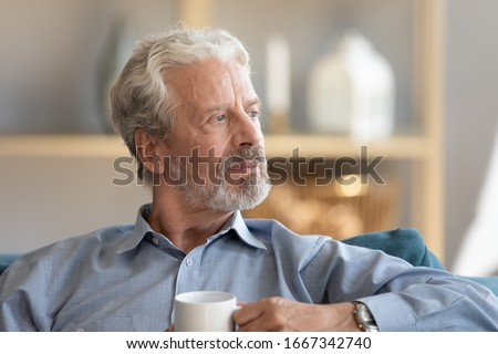 Thoughtful elderly 60s husband relax on couch at home drink tea pondering or mourning, pensive middle-aged old man sit rest on sofa in living room look in window distance thinking or dreaming
