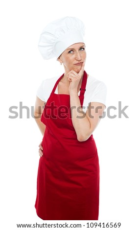 Thoughtful female chef looking away wearing hat and red uniform