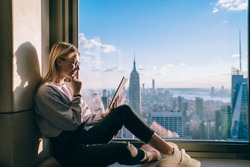Thoughtful female digital nomad thinking on writing new travel blog article while inspiring by scenery view of New York downtown sitting on window sill in modern coworking interior. Downtown office