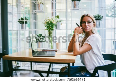 Thoughtful female entrepreneur in stylish eyeglasses thinking on developing own business sitting at table with laptop device.Contemplative owner of coffee shop looking away while working indoors