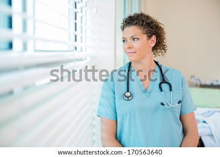 Thoughtful female nurse looking out through window in hospital room