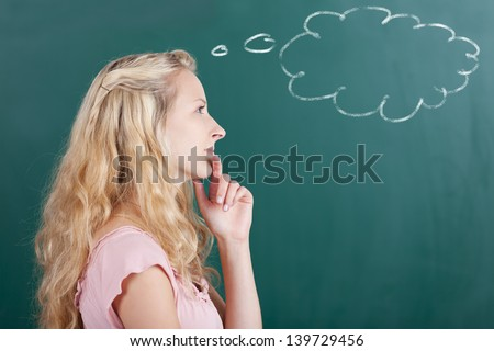 Thoughtful female professor looking away with thought bubble on chalkboard