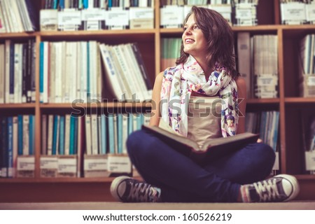 Stock Photo Thoughtful female student sitting against bookshelf with a book on the library floor
