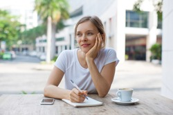 Thoughtful female student writing in copybook at sidewalk cafe. Portrait of Caucasian woman wearing white T-shirt sitting at table by university. Office worker break or education concept