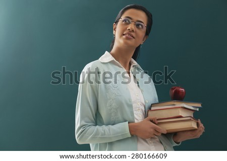 Thoughtful female teacher carrying stack of books and an apple against chalkboard