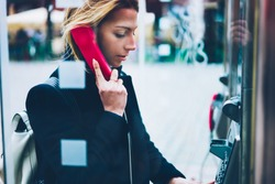 Thoughtful female tourist making call in payphone on street standing in transparent booth, young woman using public telephone operated with coins during travel for call with low prices abroad