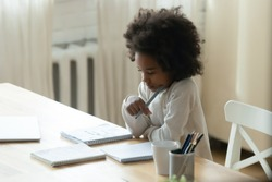 Thoughtful focused African American little girl studying at home, sitting at table, holding pen, pensive dreamy girl child pondering difficult school tasks, doing homework, homeschooling concept