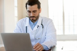 Thoughtful focused male physician working on laptop in hospital office counseling online, providing virtual appointment, studying new academic research by his speciality, thinking on electronic report
