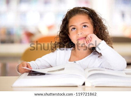 Thoughtful girl reading a book and using her imagination