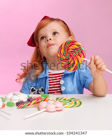 Thoughtful girl with lollipop witting by the table full of sweets