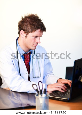 Thoughtful handsome doctor working on a computer in hospital