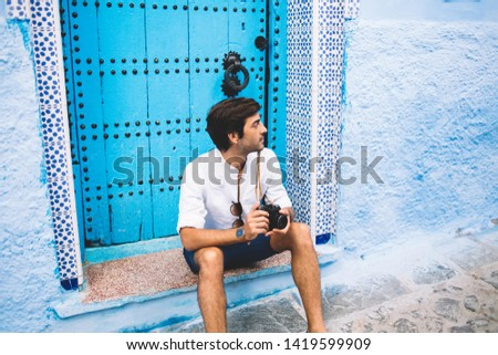 Thoughtful hipster guy with retro equipment in hands taking rest near ancient blue door thinking on idea for capture breathtaking Unesco buildings, handsome man visit Morocco during summer vacations