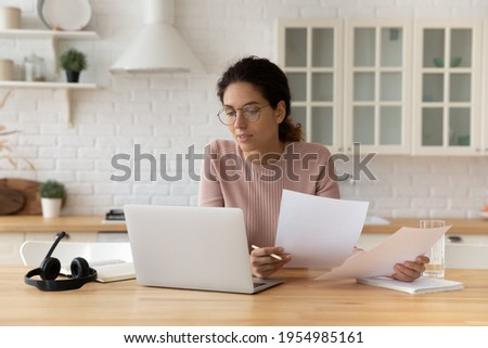 Thoughtful hispanic female sit at home workplace hold financial documents look on pc screen check data. Serious young woman think on business offer compare terms conditions in paper letters and online Foto d'archivio ©