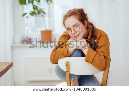 Thoughtful introvert young woman seated in a chair leaning over the back studying the camera with a pensive smile