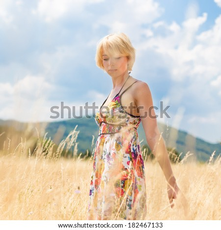 Thoughtful lady walking in the nature. Young woman enjoying the fresh air in summer meadow.