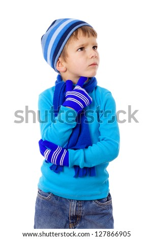 Thoughtful little boy in blue winter clothes, isolated on white