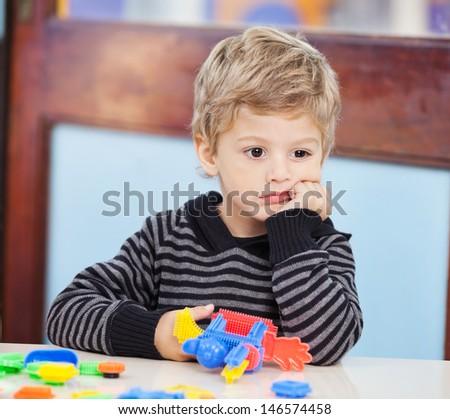 Thoughtful little boy with blocks looking away in preschool