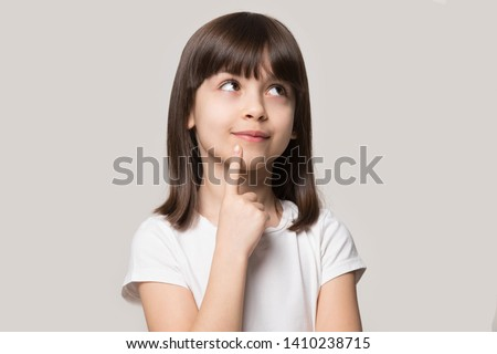 Thoughtful little girl brown-haired child touch chin with finger thinking or considering, pensive lovely daughter making decision imagining idea posing isolated on beige studio background