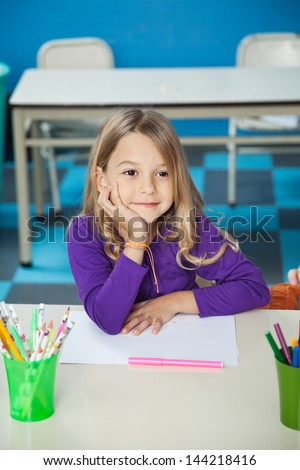 Thoughtful little girl sitting with hand on chin at desk in classroom