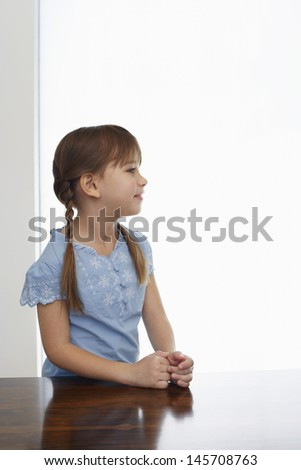 Thoughtful little girl standing at wooden table