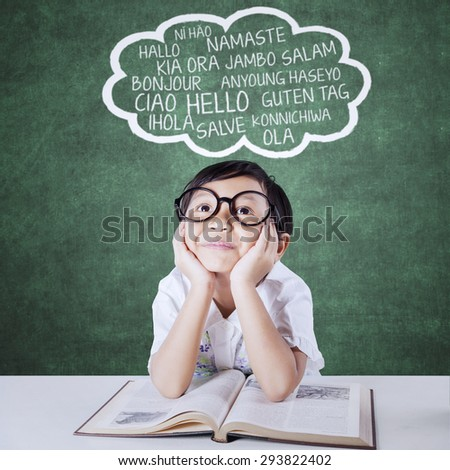 Thoughtful little girl studying multi language with a book and imagine foreign words