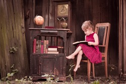 Thoughtful little girl with books and a globe in the wooden interior, vintage, retro style