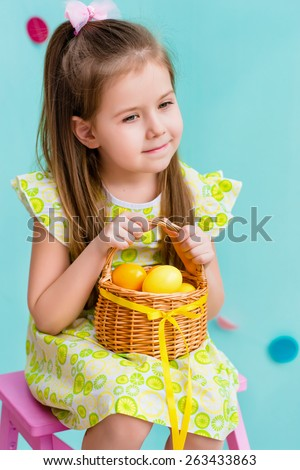 Thoughtful little girl with long blond hair wearing pink bow and holding wicker basket with yellow eggs and ribbon sitting on pink chair. Easter celebrations. Turquoise background. Studio portrait