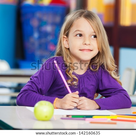 Thoughtful little girl with sketch pen and paper sitting at desk in classroom