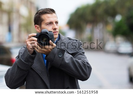 thoughtful male photographer with a camera on street