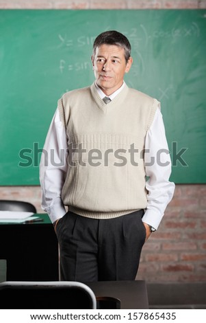 Thoughtful male teacher with hands in pockets looking away in classroom
