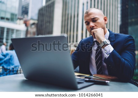 Thoughtful male trader ponder while solving problem with online business sitting outdoors in downtown, tired entrepreneur closed eyes worried about financial report uploading files on laptop computer