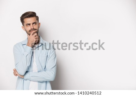 Thoughtful man holding hand on chin pose of indecision, look aside at copy space isolated on white grey studio background considering making difficult feeling doubtful about on freespace text concept
