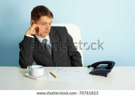 thoughtful man in the office looks at the phone