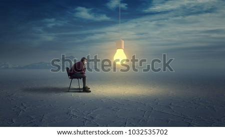 Thoughtful man in wilderness looks to a yellow light bulb coming down from the sky. ストックフォト ©