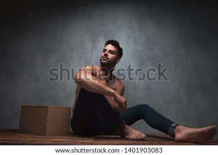 Thoughtful man looking to the side and holding one hand on his neck while being shirtless and sitting on gray studio background