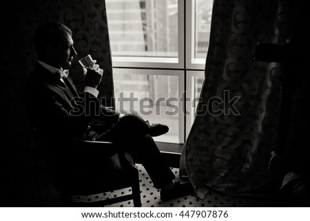 Thoughtful man sits before a panoramic window and drinks whisky #447907876